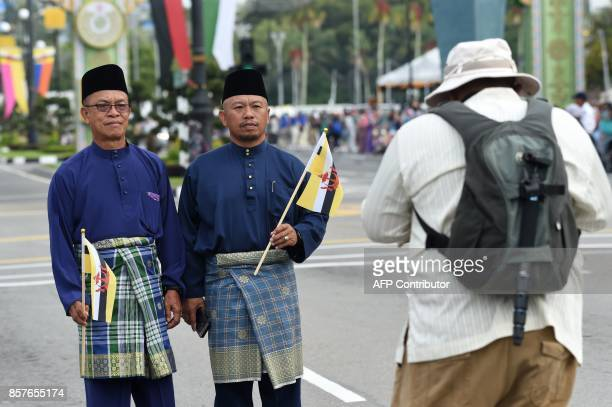 Two men pose for a photograph while waiting for Brunei's Sultan Hassanal Bolkiah to ride past on a royal chariot during a procession to mark his...