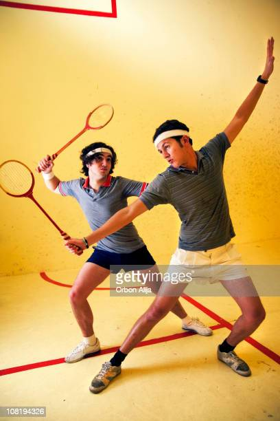 Two Men Posing and Playing Squash on Court