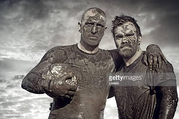 Due uomini in posa con Camicia rugby palla nel fango