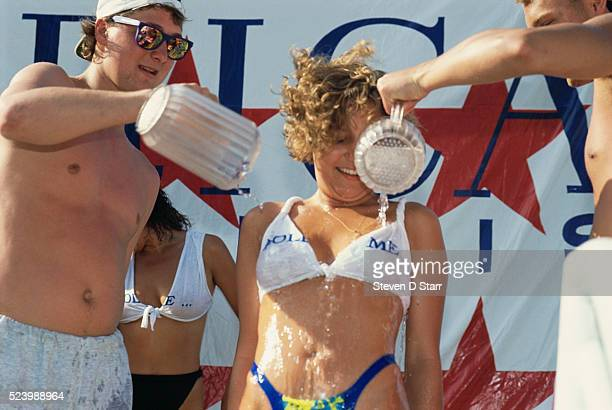 Two men pour ice water onto a wet tshirt contest participant during Spring Break in Daytona Beach