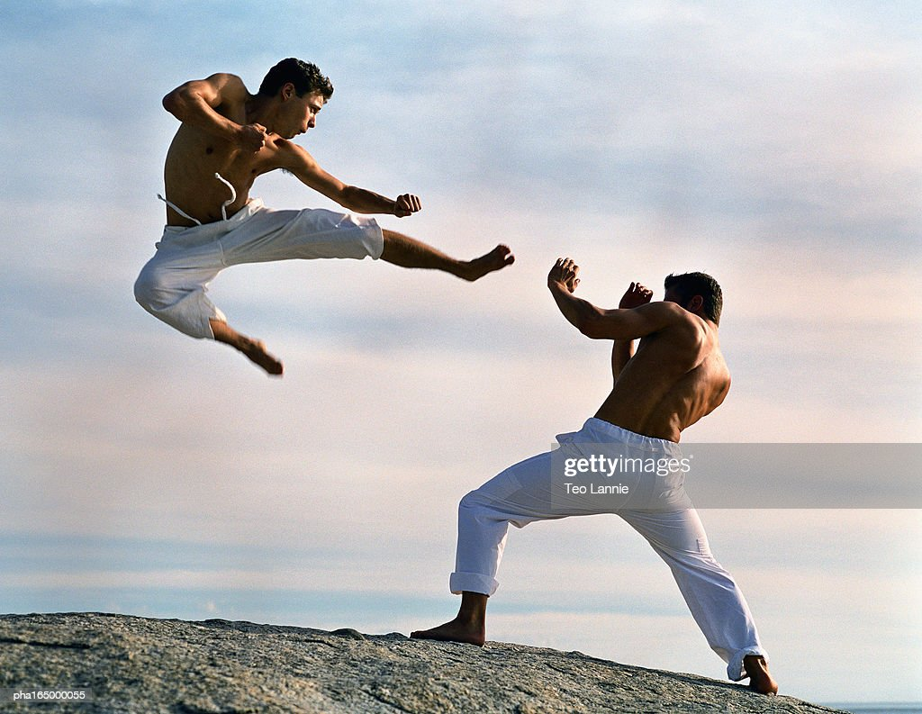 Two men practicing martial arts, one in mid-air. : Stockfoto