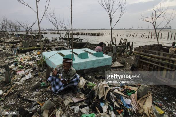 Two men pray in front of graves which are inundated by trash following the rising of sea level in Tambak Lorok village of Semarang Central Java...