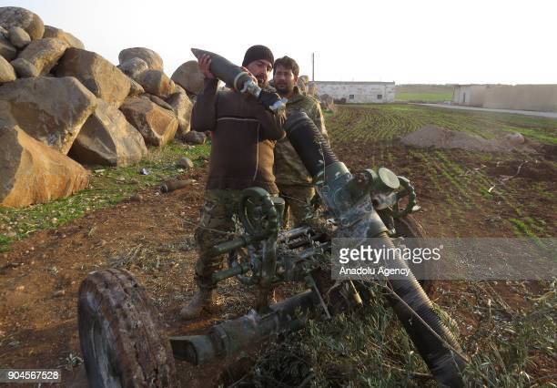Two men prepare a mortar for launch within the clashes between armed opposition group Tahrir alSham and Assad Regime forces around the Abu AlDuhur...