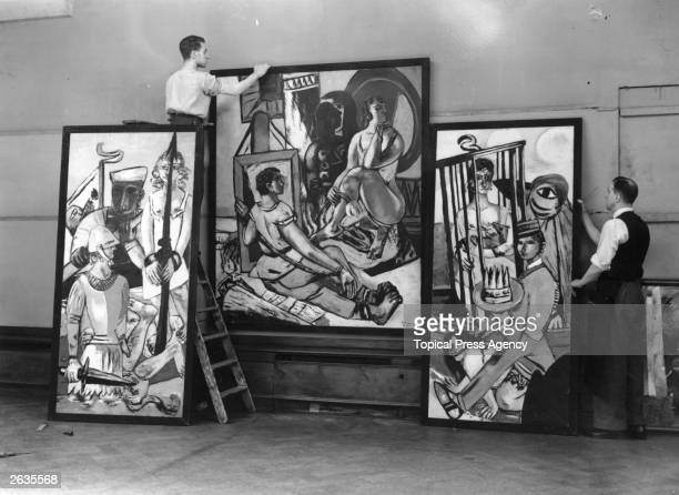 Two men prepare to hang German Expressionist painter Max Beckmann's triptych 'Temptation' at the 20th Century German Art Exhibition at the New...