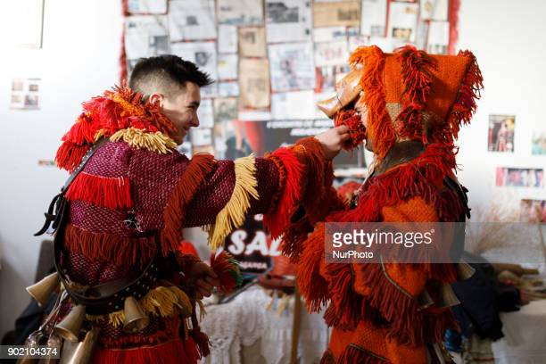 Two men prepares to take part in a winter masquerade gathering in Salsas Portugal on Saturday January 6 2018 With colorful costumes and ancient masks...