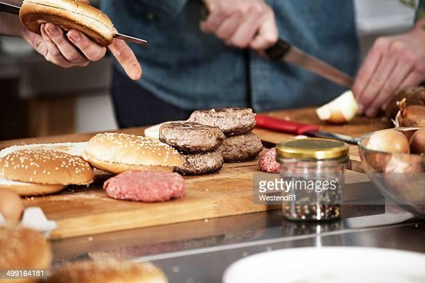 Two men preparing burgers in kitchen
