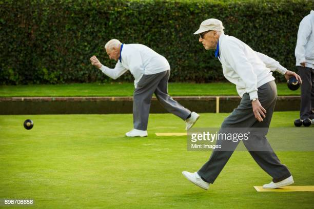 Two men preparing to deliver a lawn bowl shot, bending down and swinging their arms.