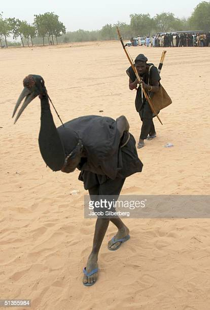 Two men pretend to be an archer and a duck to show on March 17 2004 at the Argungu Fishing Festival in Argungu Nigeria The Argungu Fishing Festival...