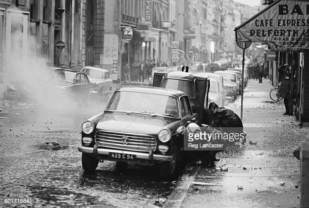 Two men protect themselves by crouching behind cars during civil unrest in Paris 30th May 1968