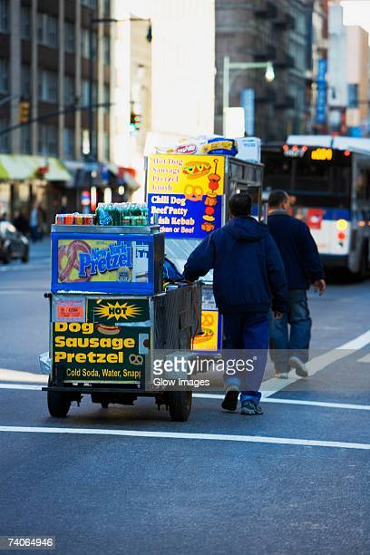 Two men pulling a hot dog stand, Manhattan, New York City, New York State, USA