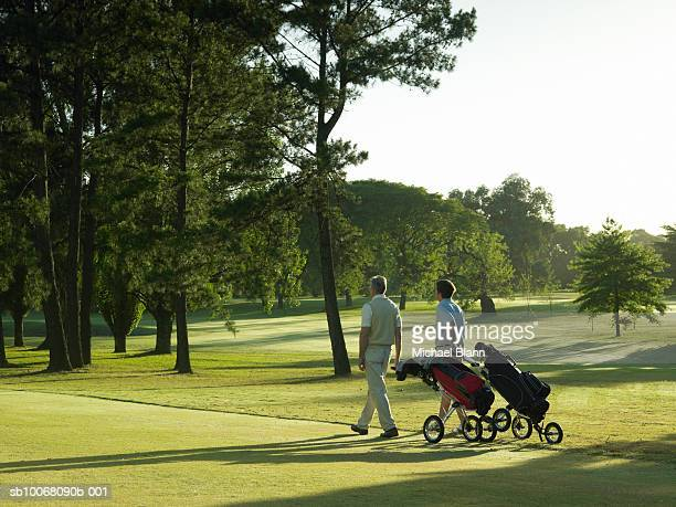 Two men pulling golf trolleys on course