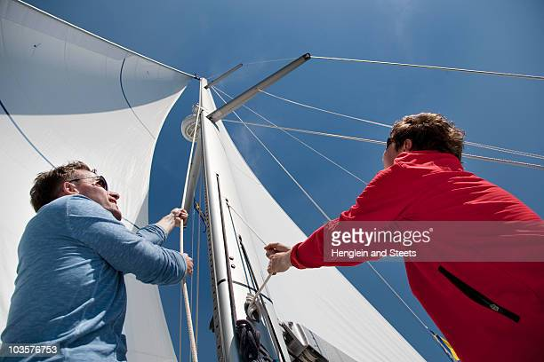 Two men pulling ropes on yacht