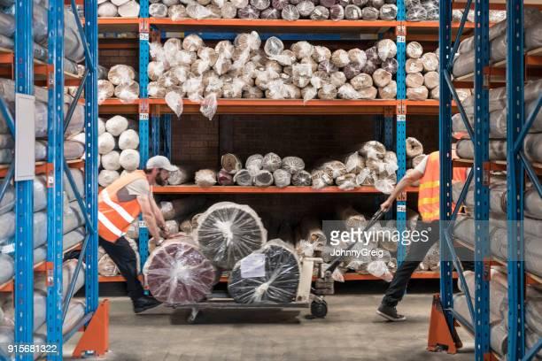 two men pulling trolley with carpets in warehouse - empurrar atividade física imagens e fotografias de stock
