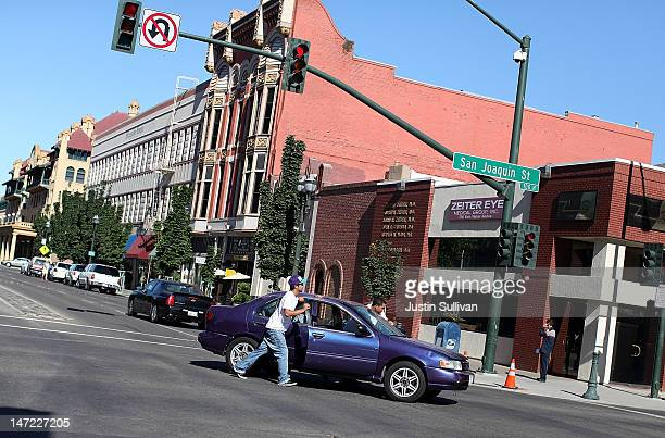 Two men push a car after it stalled on June 27, 2012 in Stockton, California. Members of the Stockton city council voted 6-1 on Tuesday to adopt a...