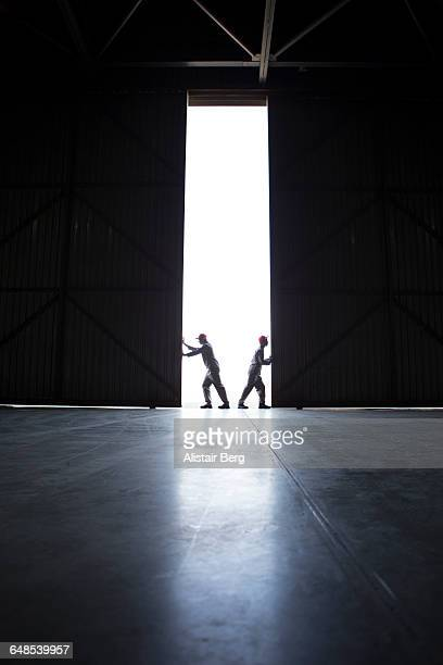 Two men pushing open doors