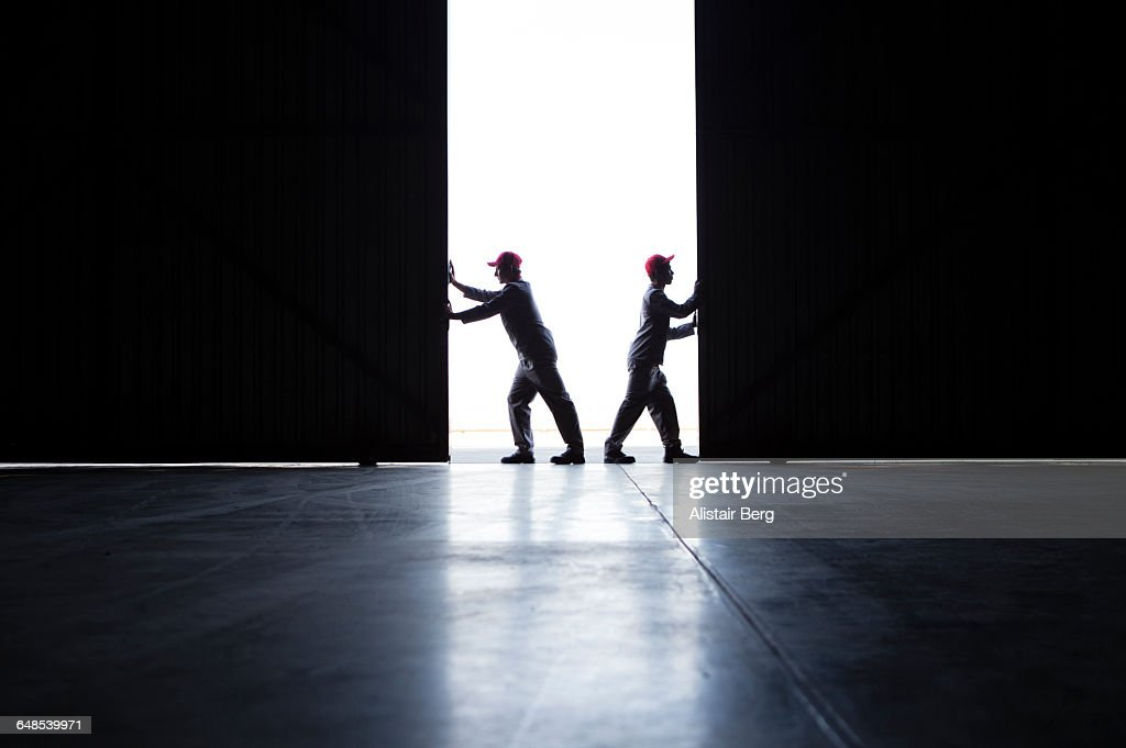 Two men pushing open doors : Stock Photo