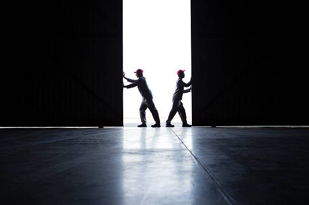 two men pushing open doors - preparation stock pictures, royalty-free photos & images