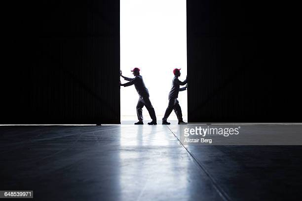 two men pushing open doors - contrasti foto e immagini stock