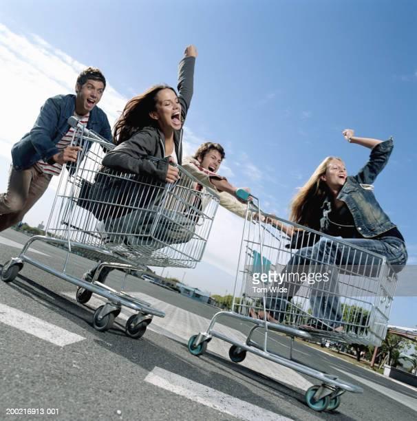 Two men pushing two women in shopping trolleys in carpark