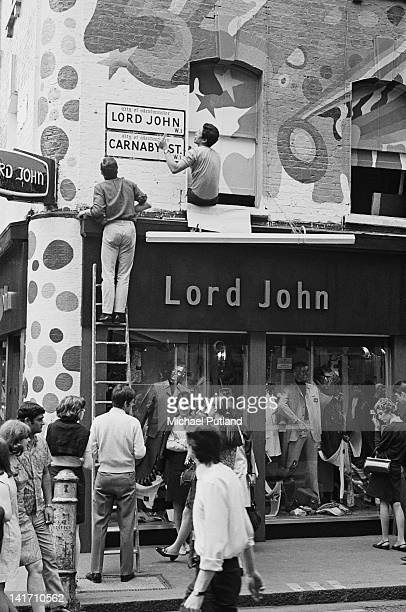 Two men putting up a sign above the Lord John boutique on Carnaby Street London July 1967