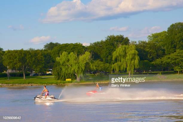 two men racing on personal watercraft in washington, d.c. - only men stockfoto's en -beelden