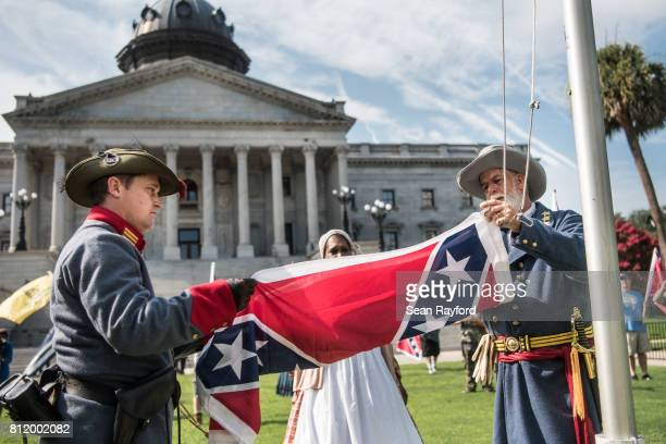 Two men raise a Confederate battle flag on the South Carolina Statehouse grounds July 10 2017 in Columbia South Carolina Today marked the two year...