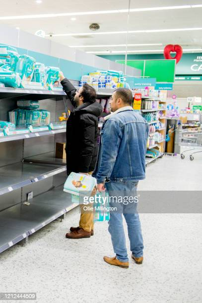 Two men reach for items as consumers leave shelves empty in a London Morrisons store as panic-buying over coronavirus continues on March 14, 2020 in...