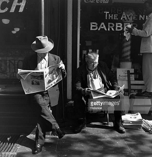 Two men read the announcements of President Franklin D Roosevelt's death in front of The Avenue Barber Shop in Washington DC April 14 1945
