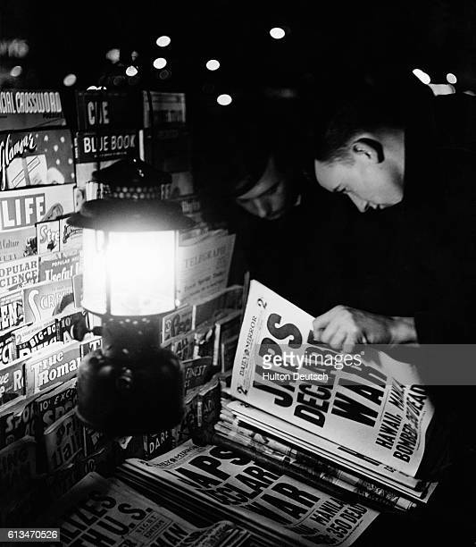 Two men read the Daily Mirror newspaper with headlines announcing that Japan has declared war They stand at a newspaper stand lit by an oil lamp in...