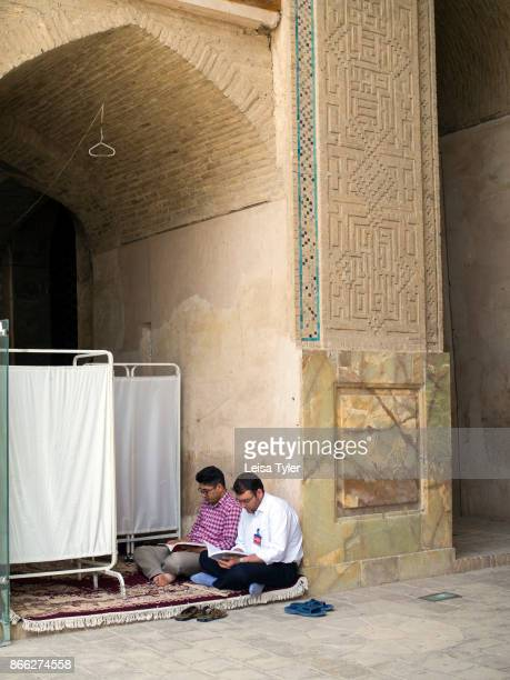 Two men reading inside the Masjede Jame in Esfahan the oldest Friday mosque in Iran The mosque is a good example of the evolution of Iranian Islamic...