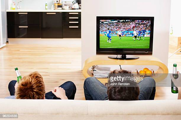 two men relax on settee watch television football