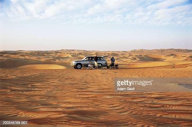Two men relaxing beside 4x4 parked on desert dunes