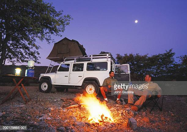 two men relaxing by campfire, dusk - night safari stock pictures, royalty-free photos & images