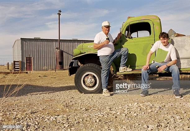 Two men relaxing with beer cans by truck, portrait