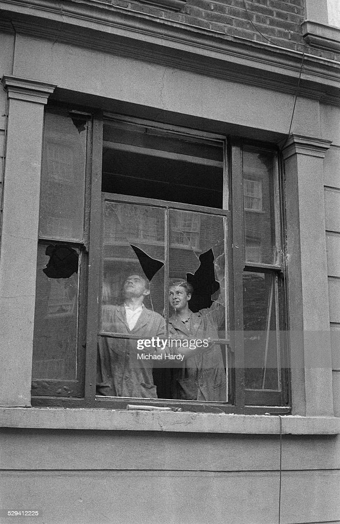 Two men remove a broken window in the aftermath of the Notting Hill race riots, London, 1st September 1958.