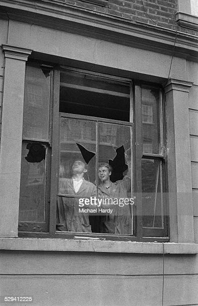 Two men remove a broken window in the aftermath of the Notting Hill race riots London 1st September 1958
