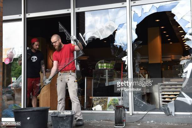 Two men remove broken windows from a destroyed shop after riots in Hamburg's Schanzenviertel district on July 8 2017 in Hamburg northern Germany...