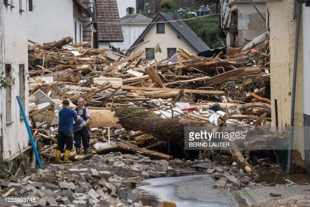 Two men remove try to secure goods from next to debris of houses destroyed by the floods in Schuld near Bad Neuenahr, western Germany, on July 15,...