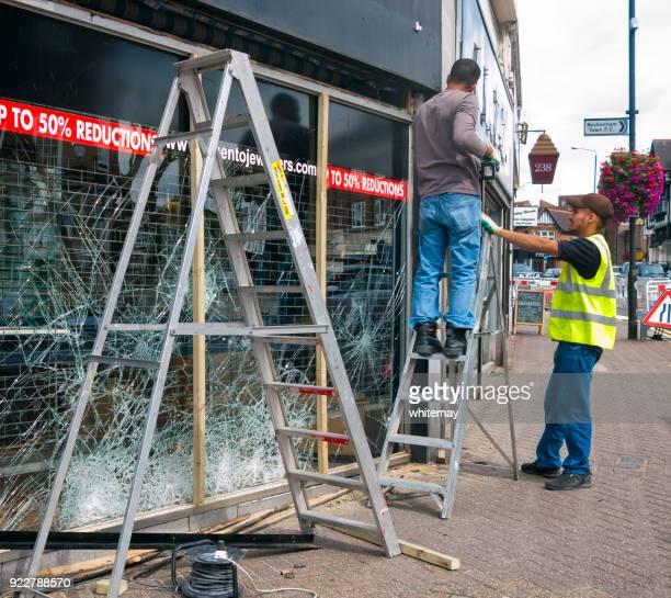 Zwei Männer ein geschändeter Fenster reparieren