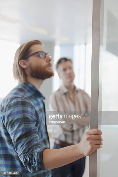 two men reviewing layout diagrams in design planning office - real estate office stock photos and pictures