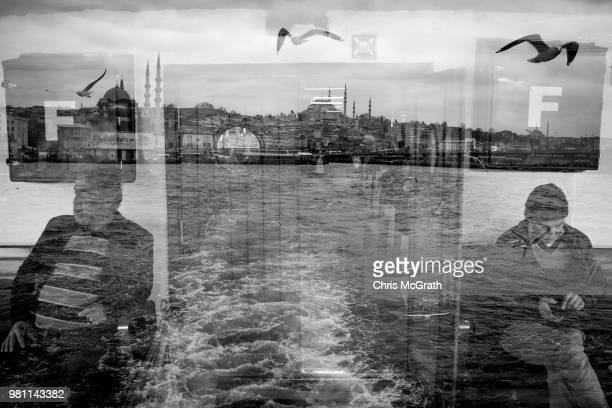 Two men ride a ferry overlayed by seaguls and the skyline of Eminonu on February 19 2018 in Istanbul Turkey With Turkey being just days away from the...