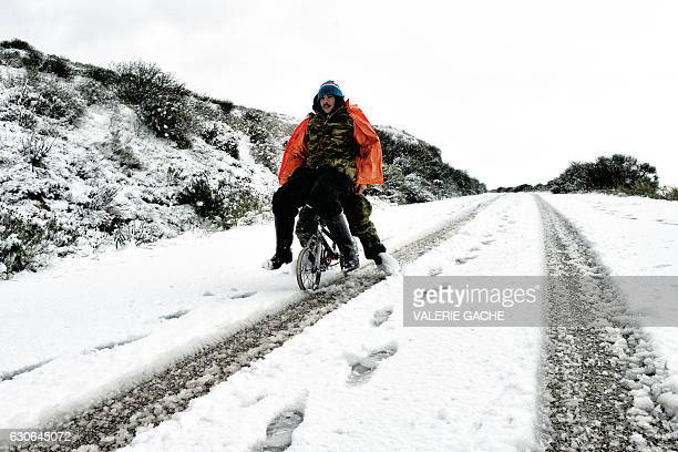 Two men ride a small bicycle on a snowcovered hill in Ancient Corinth some 80 km west of Athens on December 29 2016 Snowfall and strong winds have...