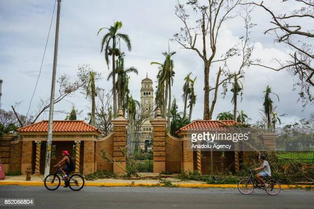 Two men ride bicycles in front of the main entrance at the University of Puerto Rico Rio Piedras campus after Hurricane Maria at Ponce de Leon Avenue...