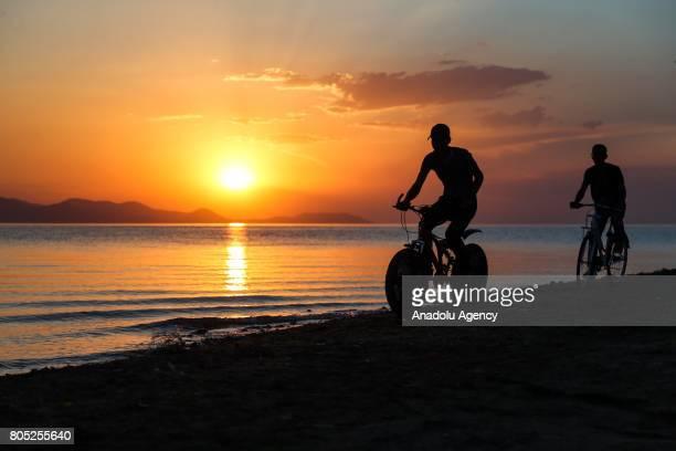 Two men ride their bikes during a sunset near Lake Van in Edremit district of Van Turkey on July 1 2017