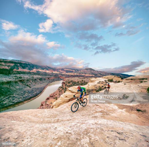 two men riding a mountain bike on an extreme sandstone ledge - robb reece stock pictures, royalty-free photos & images