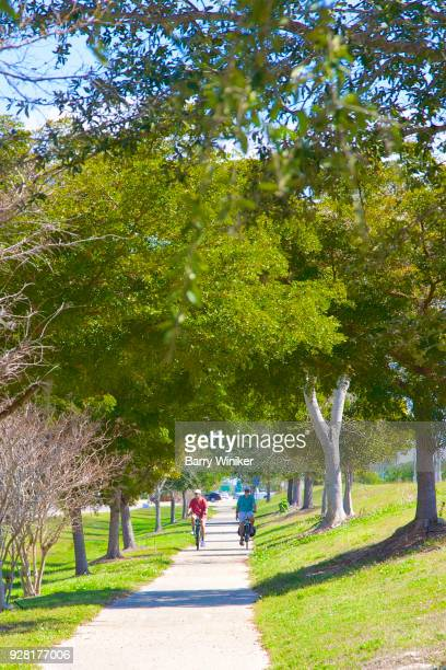 Two men riding bikes together on bike path near trees