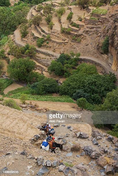 two men riding donkeys climbing towards village of tizgui, anti-atlas mountains. - men stockfoto's en -beelden