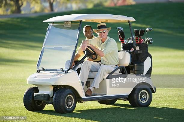 Two men riding in golf cart, smiling, portrait, side view