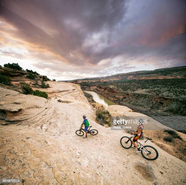 two men riding mountain bikes on an extreme sandstone ledge - robb reece stock pictures, royalty-free photos & images