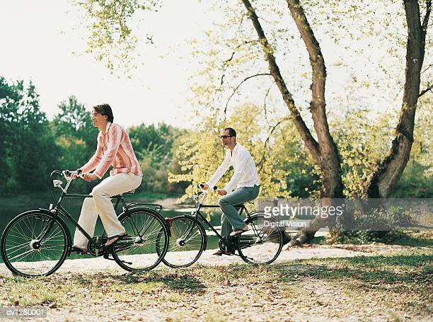 two men riding old fashioned bicycles at the edge of a lake - rivage photos et images de collection